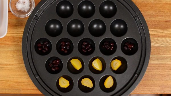 Place the chestnut pieces and the candied beans into each takoyaki mold.