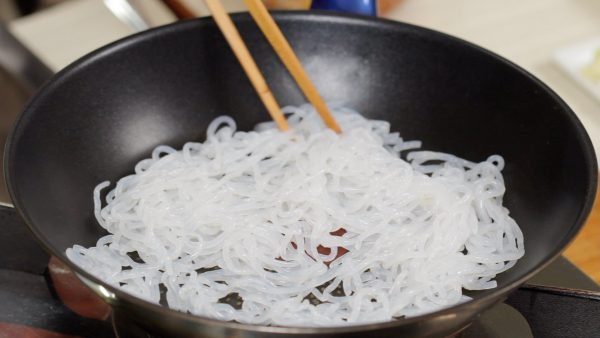 And now, let's make the shirataki pasta. Place the parboiled shirataki into a heated skillet and thoroughly stir-fry it to reduce the water. This process is important because the water will make the dish soggy and prevent the sauce from coating the noodles. When the shirataki makes squeaky sounds, it is ready.