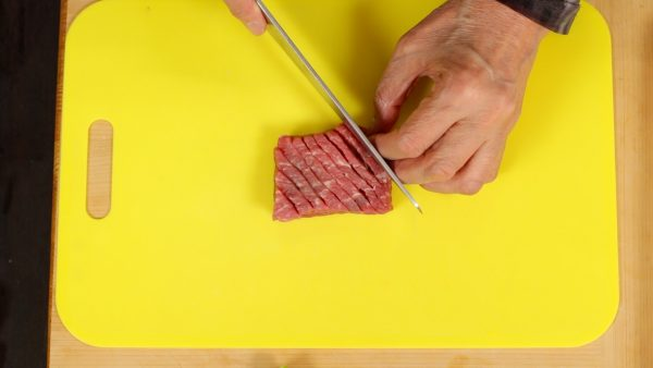 Let's prepare the ingredients. Make numerous shallow cuts in the beef steak to tenderize it. Flip it over, and make cuts on the other side.