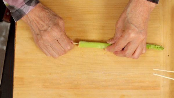 Snap off the root end of the asparagus spear. Peel off the firm skin from the bottom part so that you can boil, or use it in stir-fried dishes. Skewer the asparagus spear with a stick.