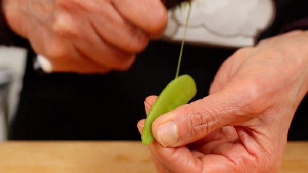 Remove the firm stringy part from the snow pea pods. Pull the string from the stem end to the tip along the pod.