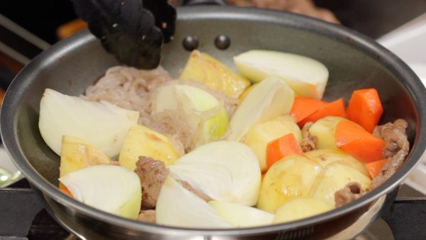 And now, add the onion and ito konnyaku also known as shirataki noodles. Stir to coat the ingredients with oil evenly.