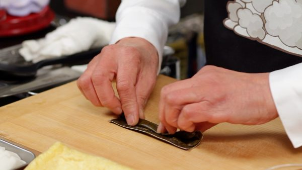 First, let's prepare the ingredients. Roll the dashi kombu seaweed and shred it as thinly as possible.