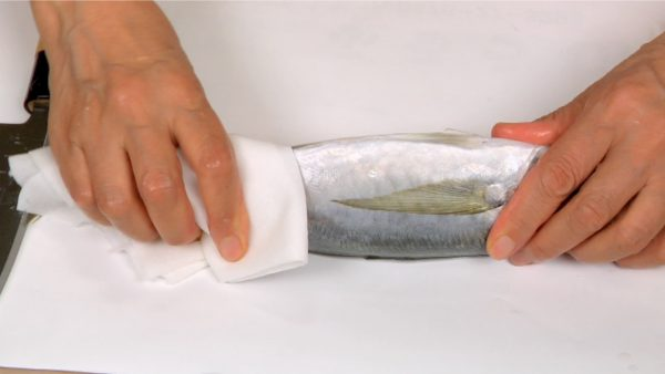 As shown, place the aji on the cutting board covered with a sheet of paper. Remove the excess water with a paper towel.