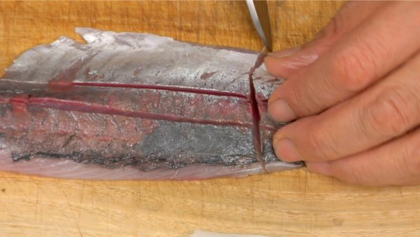 Using a long knife such as a sashimi knife, pull the blade across the fillet to cut it into bite-size pieces.