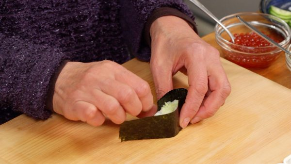 Wrap the side of the rice with the strip of nori with the glossy side facing outward. Using a rice grain, close the end of the nori.