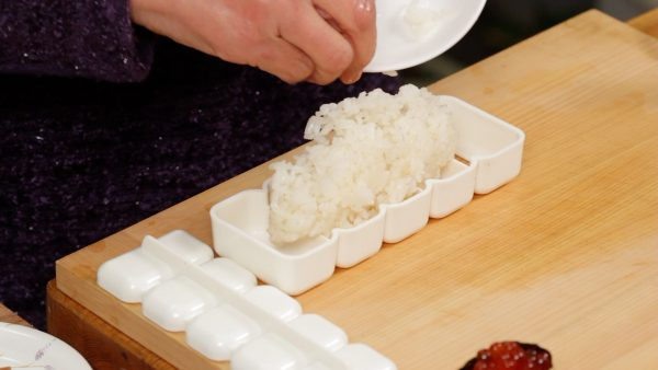 Now, we will show you how to use the sushi rice mold. Wet the sushi rice mold beforehand. Wet your hands again and measure out 100g (3.5 oz) of sushi rice.