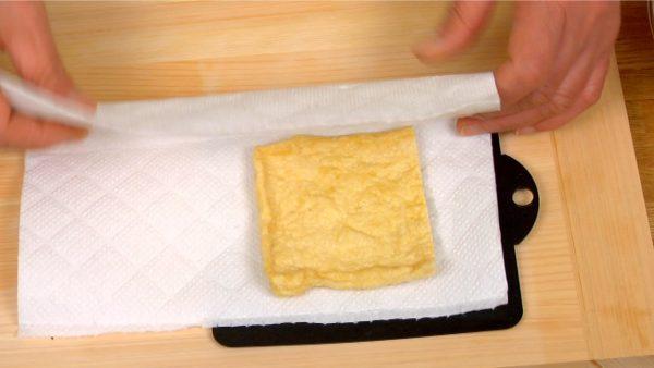 油揚げはキッチンペーパーではさみ両手で押さえます。裏に返して押さえ、油を吸い取ります。