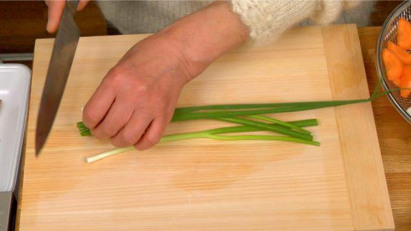 万能ねぎの根を切り落とし、積み重ねて小口切りにします。