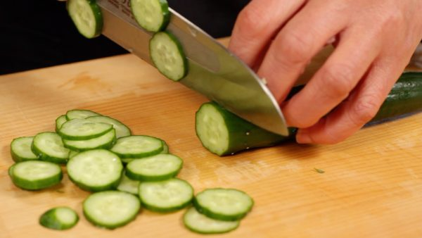 """Trim off both ends of the cucumber. Slice the cucumber into 2 mm (0.1"""") rounds."""