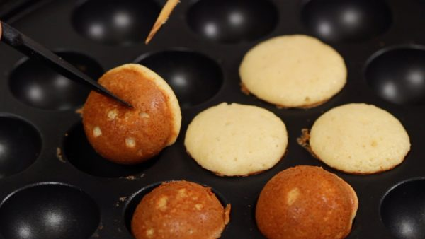 When the bottom of the castella is thoroughly browned, flip the pieces over. The half browned round shape looks like a bell, doesn't it? Suzu means bell in Japanese so that is why we call these suzu castella.