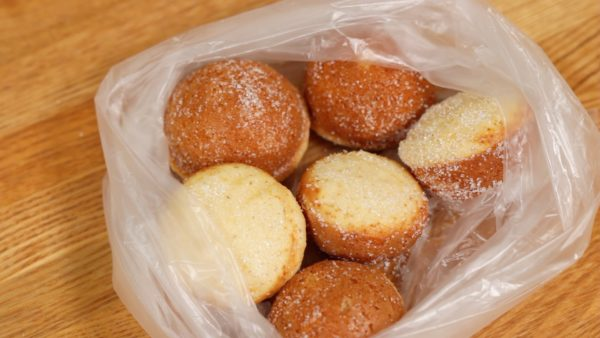 When the suzu castella are slightly cooled, place them into a plastic bag with sugar. Slightly cooling the castella will help them to coat thinly and evenly, making them more presentable.